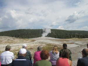 People sitting in anticipation of Old Faithful