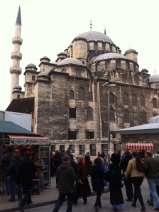 Crowds pass by the Yeni Mosque near the water front