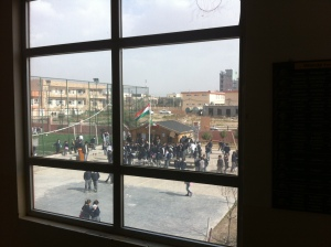 Primary school students gather around the Kurdish flag during recess.
