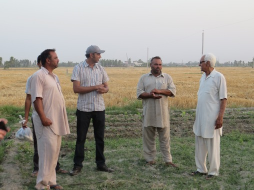 Monu (in the cap) and Uncle Ji (on the right) talking with the farm hands