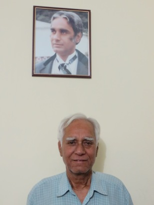 Uncle Ji below a picture of himself taken at my aunt's wedding in the early 80's