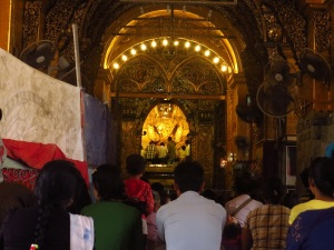 locals worship in front of the gilded Buddha