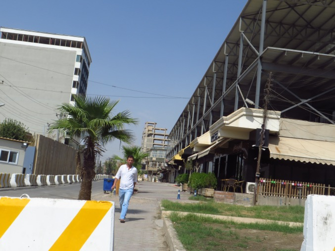 When you're taking photos clandestinely while walking because Kurdish security forces are staring at you. O'Ccaffe is the first awning on the right, and the bomb exploded where the wall now stands on the left