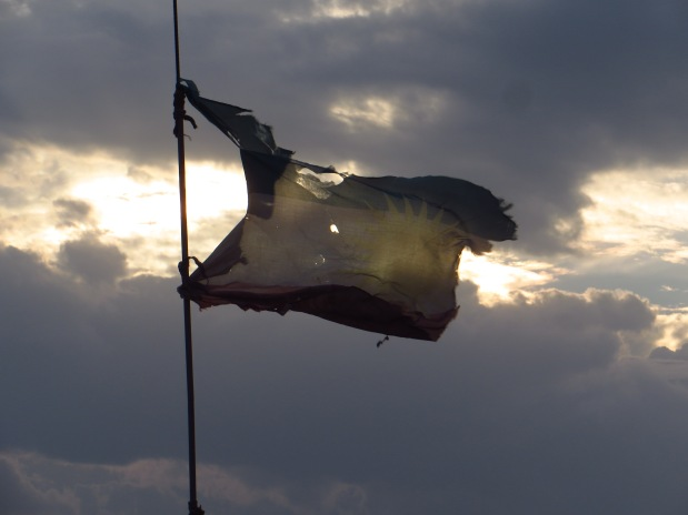 A tattered Kurdish flag waving wildly in the wind